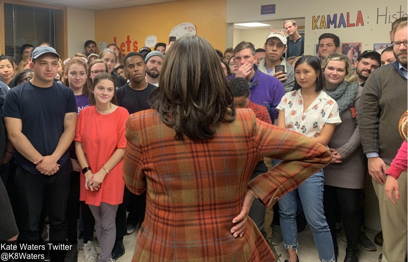 This image has an empty alt attribute; its file name is Kamala-Valentino-Orange-Plaid-Jacket-From-Back-Oct-31-2019-Adressing-Large-Group-of-People-Kate-Waters-@K8_Waters-Tw-1.jpg